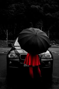 woman with umbrella standing in front of car