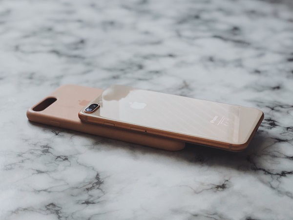 rose gold cellphone on marble counter with pink case