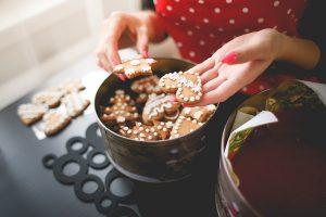 Young Woman Showing Freshly Baked Christmas Cookies