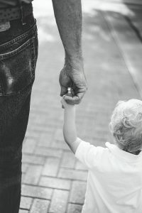 boy holding hands with person on road