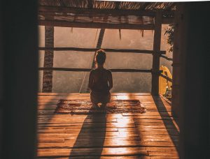 woman meditating on floor with overlooking view of trees